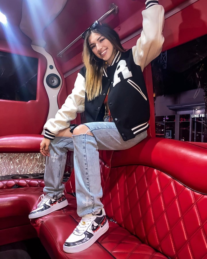 Ahlyssa Marie inside a party bus sitting on top of the red couch.