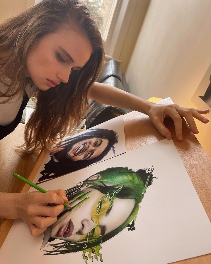 Julia Gisella applying the finishing touches on her art of Billie Eilish, with an art of Bob Marley also on the scene.