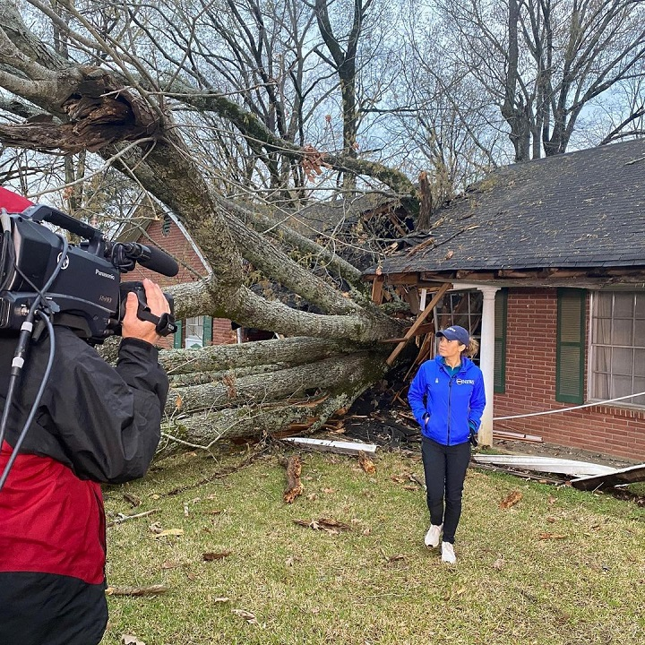 Ginger Zee at the scene after a disaster being filmed in front of a house toppled by a massive broken tree.