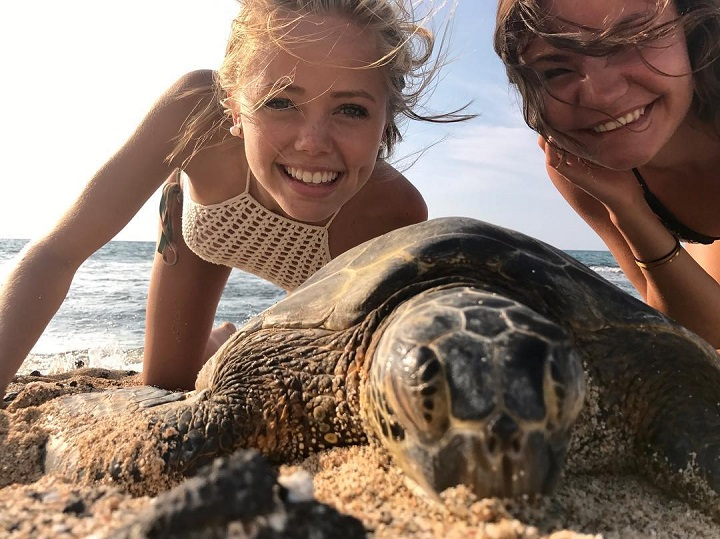Annalisa Cochrane (left) with her friend (right) and a turtle in front of her as a selfie.
